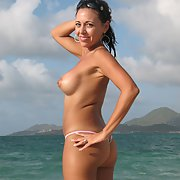 Sexy and busty milf in only a thong showing cameltoe on beach