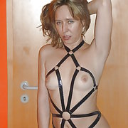 Candy in a black harness with overkneeboots